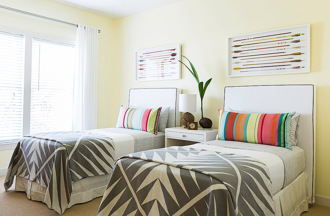 "With the beach house being a revolving door for family and friends all year round, the guest room is occupied just about every weekend with adults or kids. As a ""bright and happy"" counterpoint to the rest of the home, Matthew brought in cheery hues, slipcovered headboards, and Pendleton blankets ""so that anyone could feel comfortable here at any age."""
