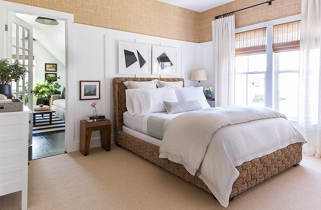 "In the master bedroom, woven textures take center stage, from the Merida carpet and the Ralph Lauren wall covering to the luxurious woven bed (""How can I not be happy about that?""), while black-and-white paintings by Matthew are displayed just above. ""I really wanted a shot of black. That's something that wasn't anywhere else in the home,"" he says."