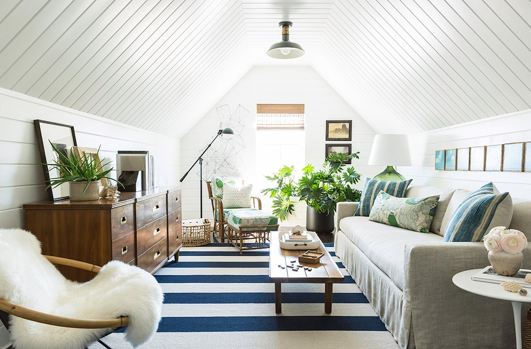 """Just off the master bedroom, the attic living space brings together Matthew's love of blue and white and his husband's love ofgreenery. """"We really wanted to finish off the attic space and make it like our own private living room,"""" says Matthew. """"It's funny, coming from New York, where space is a luxury: It'sone of the things we enjoy about the home, but even in that spaciousness my favorite room is probably the smallest room in the home."""""""