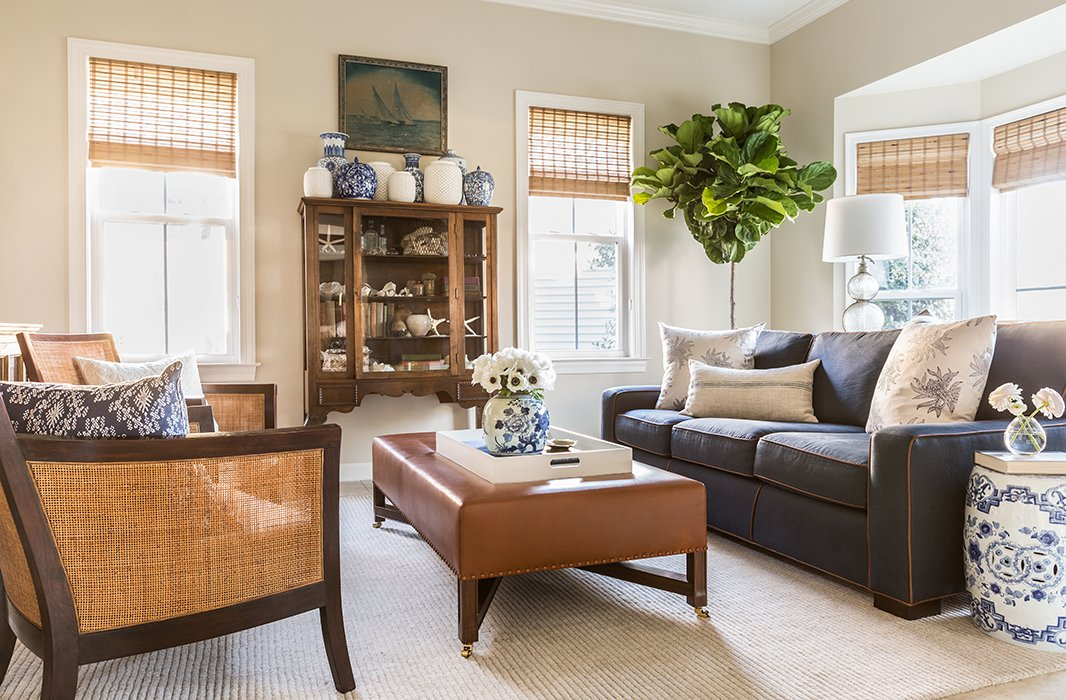 """The living room, located behind French doors just off the entry, is dressed in a beachy palette of blues, whites, and woven textures. Because it's where movie nights take place, polished practicality was top of mind. """"The sofa is a dark color because I wanted it to be durable and not be afraid of popcorn spills,"""" Matthew explains. """"And aleather ottoman is very durable and forgiving. If there's a mark, it just gives it a story and a new life essentially."""""""