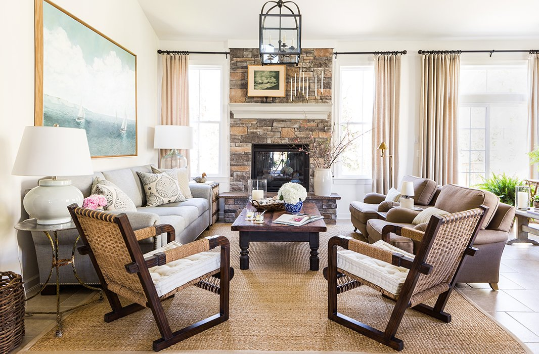 """The open-floor family room is the core gatheringspace with its soothing palette of neutrals and natural textures, sumptuous seating, and gigantic brick fireplace. Until recently, it was also an internet dead zone. """"It really forced people to talk, have a cocktail, and enjoy each other's company. I loved that about it,"""" Matthew says."""