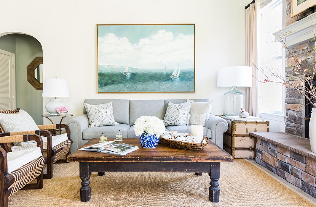 """The family room is anchored by an old worktable salvaged from a barn and """"cut down to cocktail-table height,"""" while the large seascape is one of several paintings in the home by Matthew. """"I'm the oldest of three, and we all painted growing up,"""" says Matthew, adding with asmile, """"My father always wanted a fine artist in the family, but he still hasn't gotten one."""""""