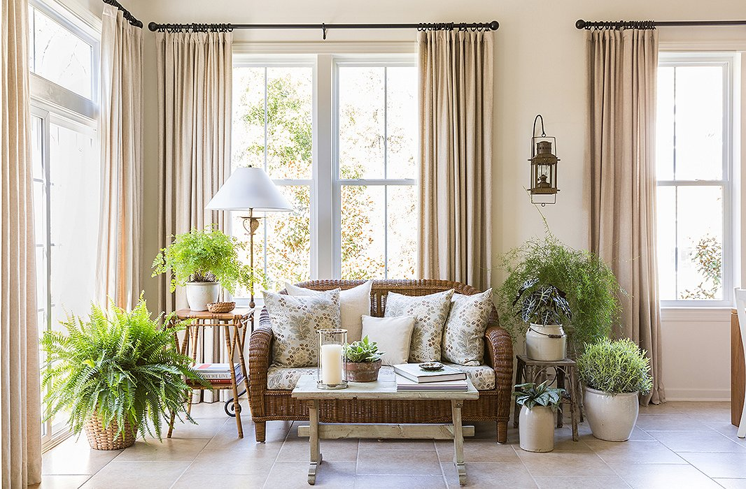 "The lush corner lounge area is planted with ferns and other leafy greenery by Matthew's husband, Zane, an avid gardener. ""We have it set up almost to feel like a sunroom with plants,"" says Matthew, who upholstered the settee in a pretty floral print and surrounded it with antique tables found locally."