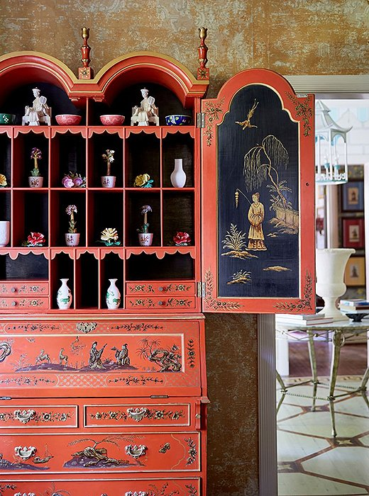This lacquered cabinet boasts both intricate carvings and elaborately painted scenes.