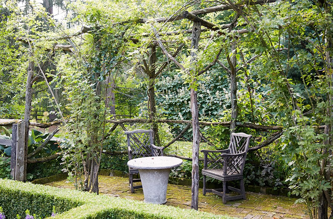 Antique chairs and a stone table beneath a rustic pergola, made from locust saplings that had been cut down, provide a quiet resting spot in the formal garden.