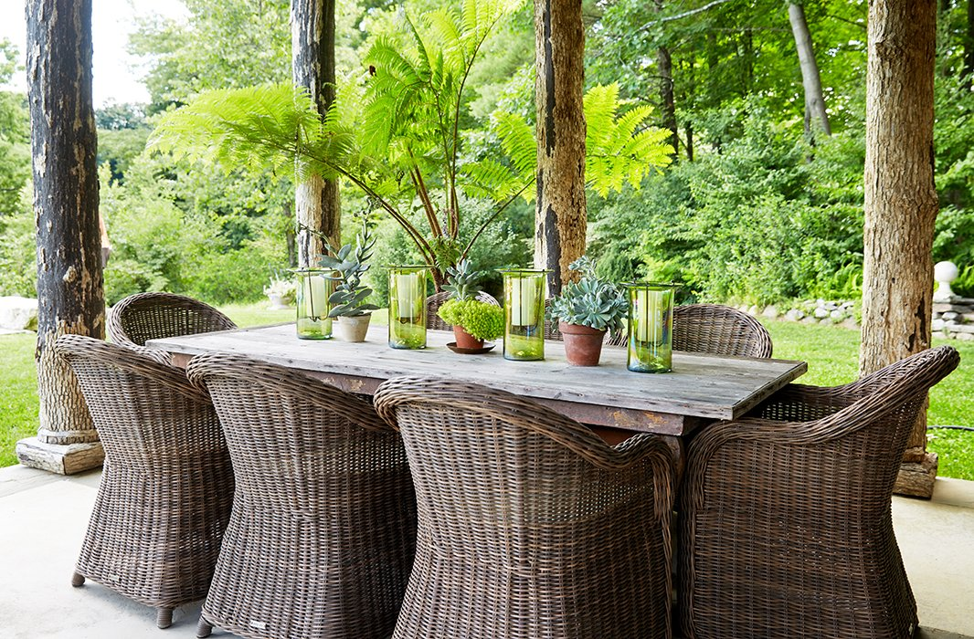 Bunny hosts many summer lunches inthe pool house at the19th-century French farm table, which isgroupedwith wicker diningchairs by Vandecasteele Marc & Co.