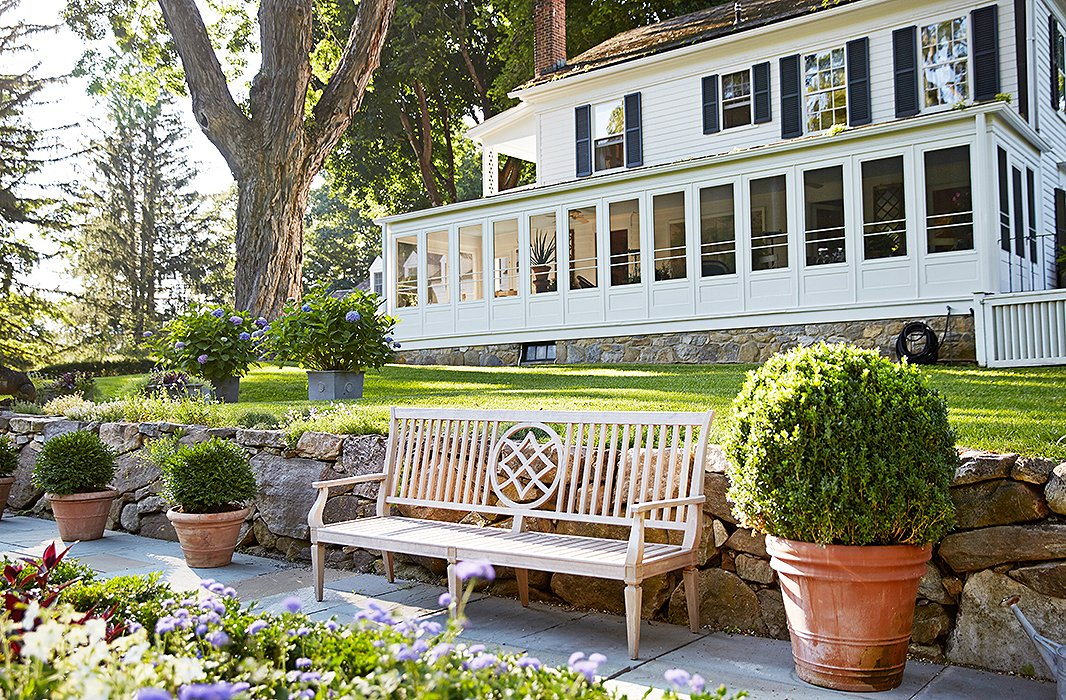 This carved wooden garden bench is one of four that line the walkways framing the sunken garden, which lies just beyond one of the home's screened-in porches.