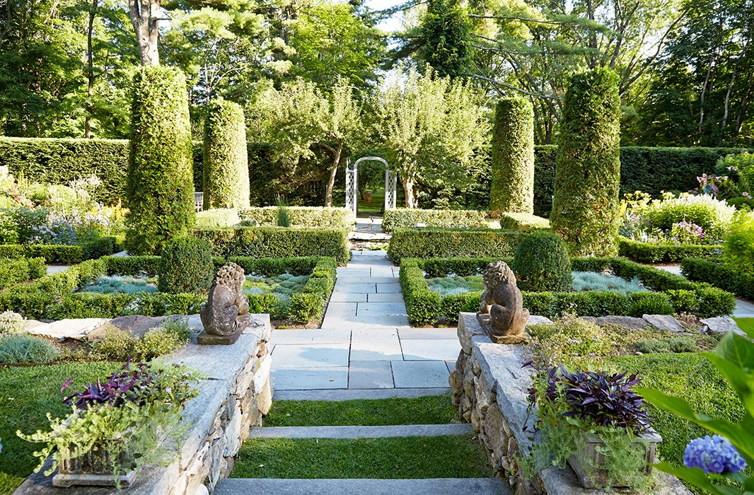 """This is the garden that John and I see from the porch,"" says Bunny of the sunken garden, which is anchored with a koi pond. ""I had a stone wall built to terrace the land. You have the sensation of moving from one space to another as you walk down the six big, wide steps that lead to the garden.""<br />"