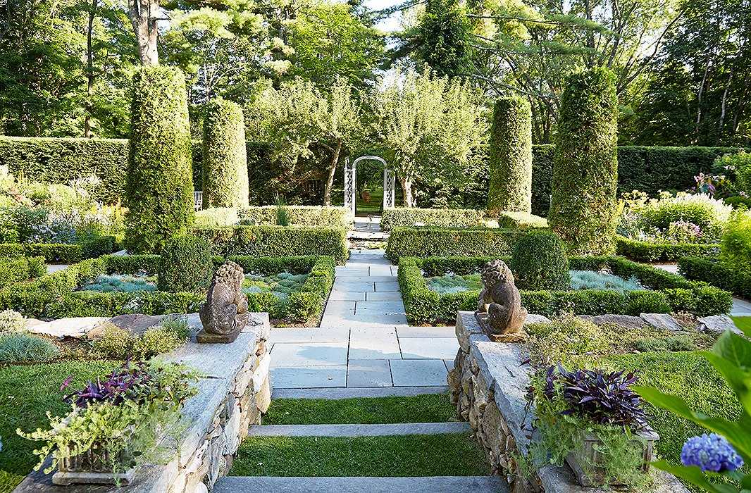 """This is the garden that John and I see from the porch,"" says Bunny of the sunken garden, which is anchored with a koi pond. ""I had a stone wall built to terrace the land. You have the sensation of moving from one space to another as you walk down the six big, wide steps that lead to the garden."""
