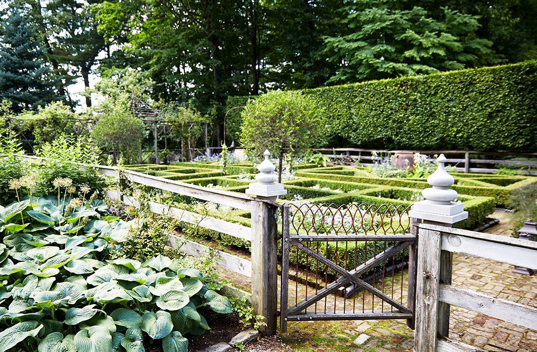 Bunny's formal garden, lined with 12-foot-high hornbeam hedges, is ever-changing, with new combinations of colorful blooms planted each year. Planning begins inwinter, when she and John sketch it all out.
