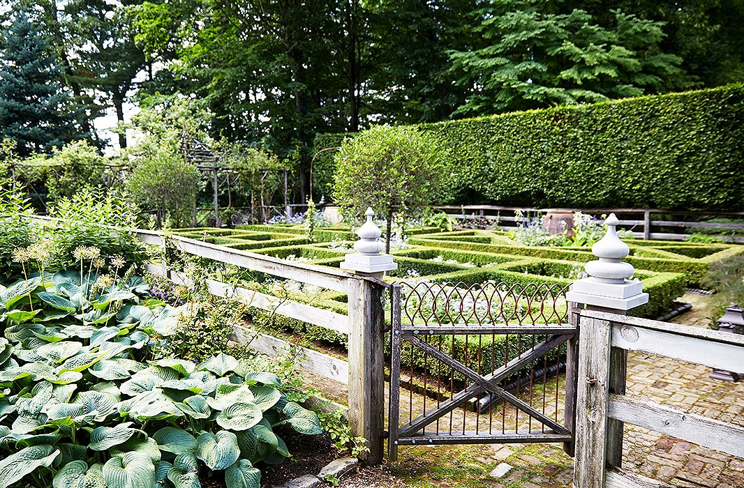 Bunny's formal garden, lined with 12-foot-high hornbeam hedges, is ever-changing, with new combinations of colorful blooms planted each year. Planning begins in winter, when she and John sketch it all out.