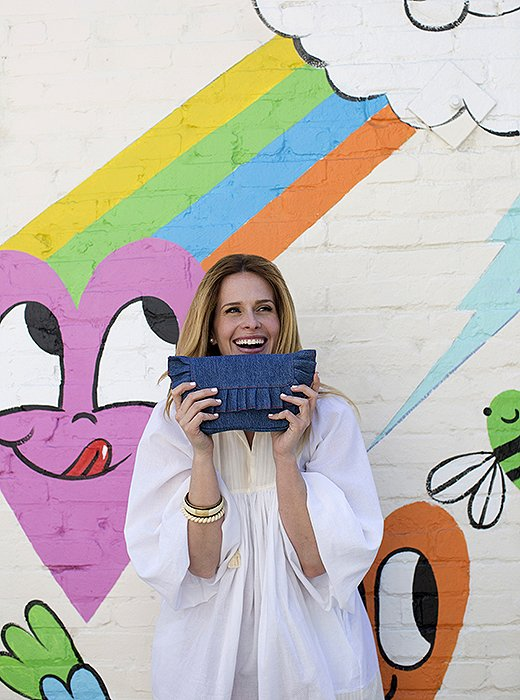 Erin holds her denim Kathleen waist bag in front of the Paul Smith shop's revolving painted wall at Melrose Place.