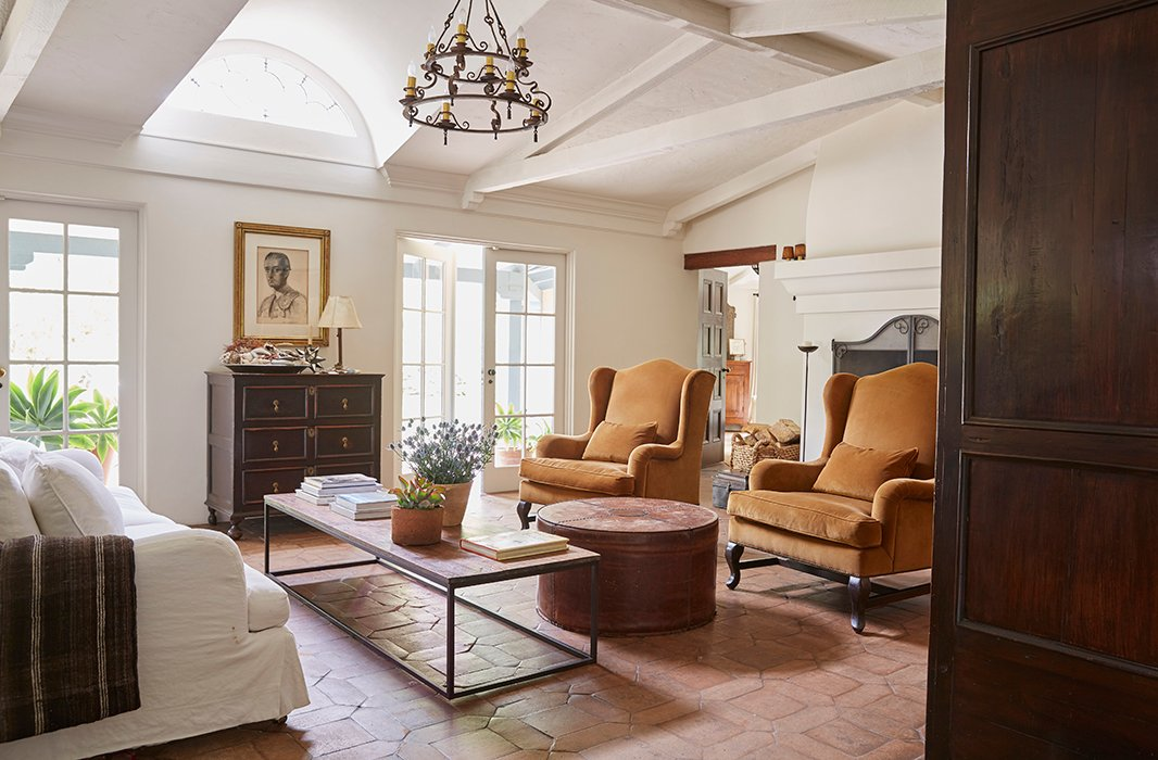 "Kendall and David painted many of the dark exposed beams white to lighten things up. A George Smith sofa and two vintage armchairs suit the long rectangular room. The large leather ottoman? ""It's a Kendall Conrad original,"" she says."