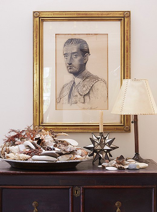 "Kendall's father, an artist, sketched the portrait of a matador. Shells from family trips spill out of a silver tray. ""Some are from the Maldives, Hawaii, Majorca—we always bring some back,"" Kendall says. The chest is Spanish and conceals the television."