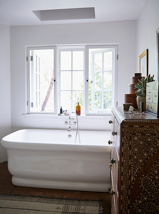 """I spend a lot of time in this tub,"" says Kendall. ""To me, the ultimate luxury is a hot bath with salts and essential oils."" The designer logs a lot of reading time here thanks to the natural light streaming from the window and skylight. The tub and fixtures are by Waterworks. Another vintage Moroccan rug covers the floor."