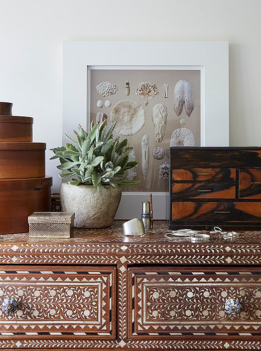 "An array of textures tops the Indian inlaid bureau in the master bath. ""The little snakeskin box and a tigerwood set of drawers hold my jewelry,"" says Kendall. ""The photo is by my friend Charles Fine, an L.A. artist. His pictures of nature really inspire me."""