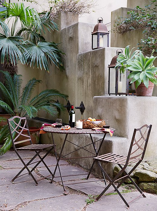"In one of the gardens, a bistro set stands ready for an idyllic rendezvous. ""That's David and my little spot,"" says Kendall. ""We like to sit there in the evening and have some wine."" A leopardwood bowl holds blood oranges from one of the citrus trees."