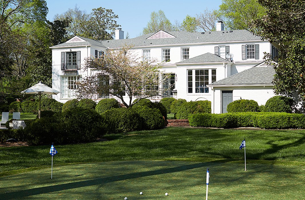 The lawn of the 1942 house has much of its original plantings and trees, but the couple added a little putting green near the pool.