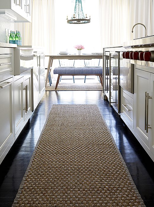 """I wanted to cut all the darkness of the floors,"" Alex says, ""so we lined each area with sea-grass rugs—they are inexpensive and durable."" And they feel good on the feet—especially in a place like the kitchen galley."