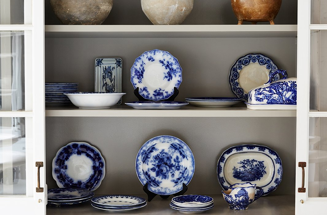A display cabinet showcases flow blue china that Darryl has collected over the years. Most of the pieces are hundreds of years old and originated in England, Prussia, and China.