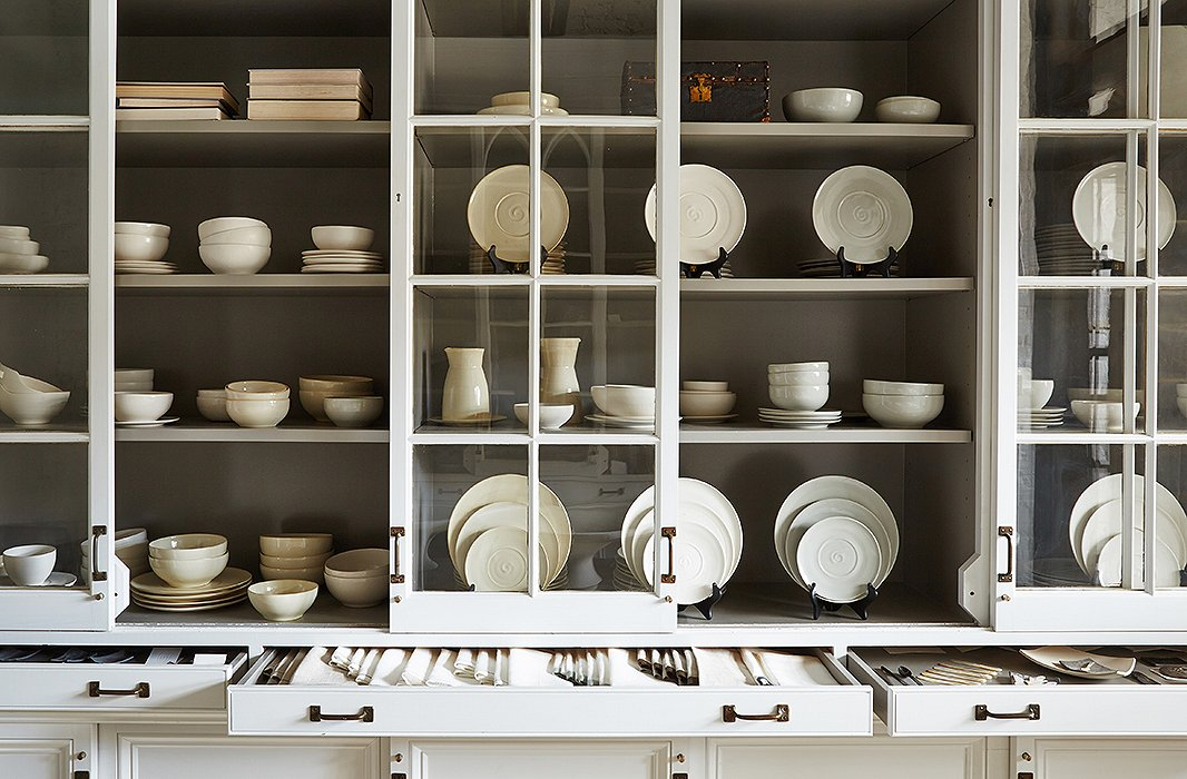 Primitive vessels, dishes, bowls, and tableware created by Darryl with ceramicist Ani Kasten fill the display case. Darryl designed the display around panel doors salvaged from the butler's pantry of a historic Georgetown home.