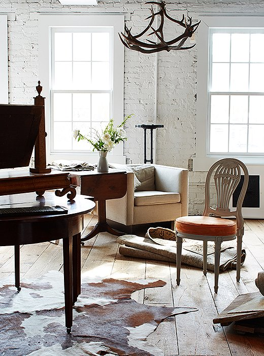 "Timeless designs, including American antiques (""A piece is timeless when it has appropriate scale and clean lines—American antiques are very clean-lined"") and upholstered pieces by Darryl, are mixed in with antique rugs, hides, and an antler chandelier."