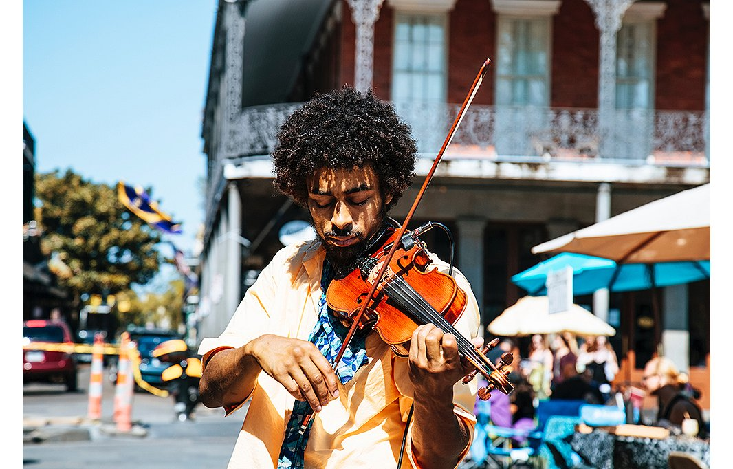 Music, of course, is partof New Orleans's DNA. Beyond the city's annual Jazz Fest, street musicians like this violinist bring a moment of melodic solace amid the city's bustling neighborhoods. Photo by William Recinos/Unsplash.