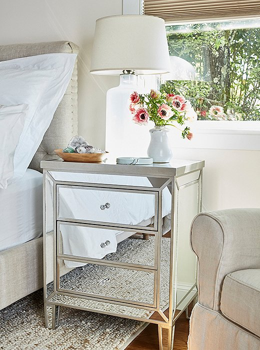 Jenn chose a mirrored nightstand from One Kings Lane to reflect the sunshine and brighten up the already light and airy space. The wooden bowl holds her crystal and rock collection, while the small plate displays some of her jewelry—a few items of which are on cross-country loan from Sarah.