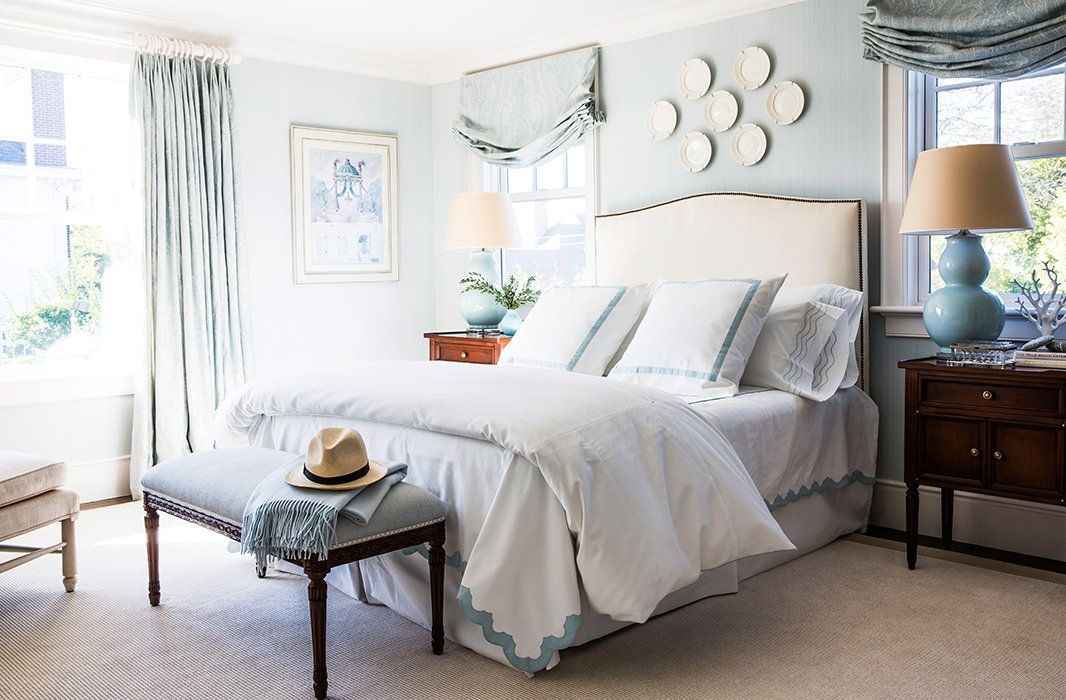 Our stylists agree that a tan headboard, light or dark, makes a soothing neutral backdrop. For always-stylish bedding to go with it? Think blue and white.