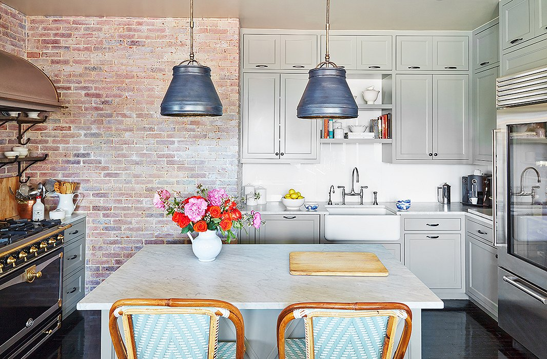 The designer had the bistro-style barstools custom-made by TK Collections to match the cabinetry. She echoed the industrial feel of brick in a pair of weathered zinc pendants over the island.