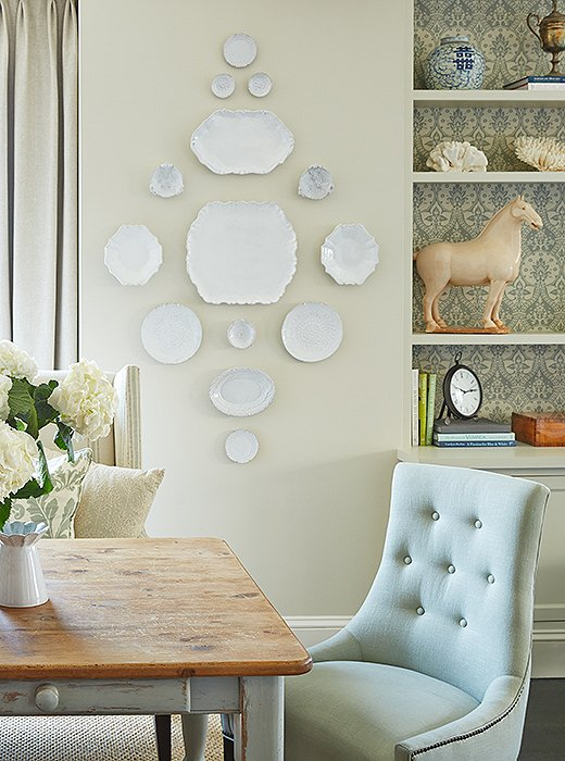 To carrythe kitchen's soothing color scheme into the adjacent areas, Wolf painted the base of her client's antique farm table in a Farrow & Ball light blue (which matches a new coffered ceiling in the living room) and lined the dining room bookshelves with a soft blue-and-cream damask wallpaper.