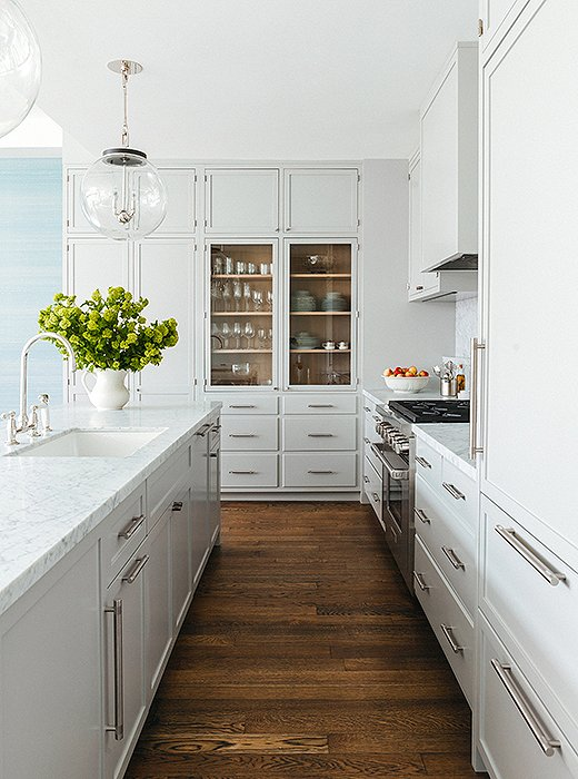The McGraths mixed open and closed storage in the kitchen for a clean and composed look. Cabinets in Benjamin Moore's Cliffside Gray.