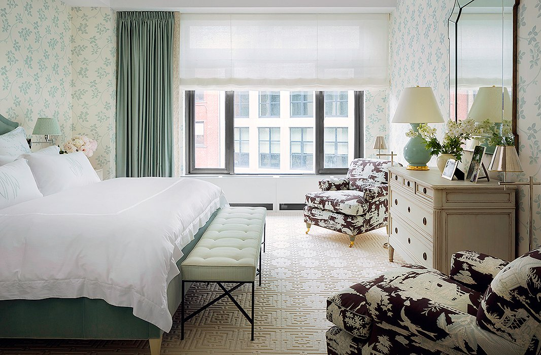 Layered patterns—a toile, a floral, and a geometric—harmonize in the master bedroom thanks to a serene color palette.