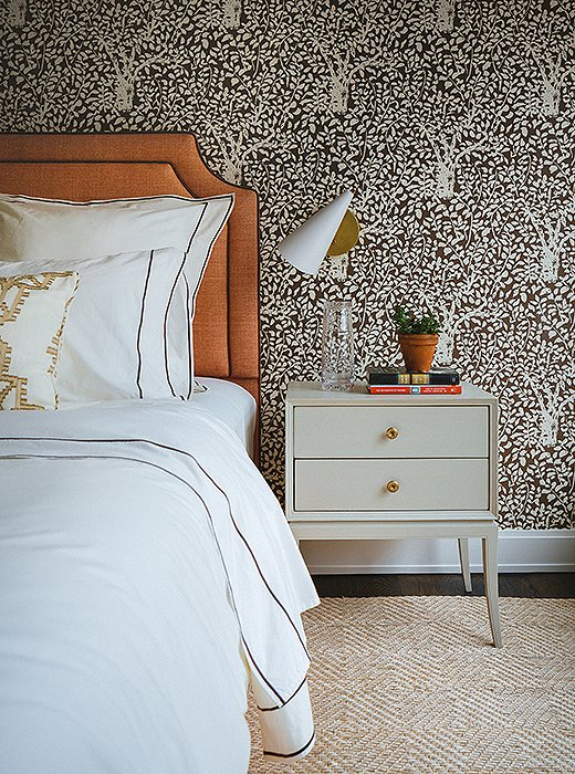 Statement wallpaper turns the loft's guest bedroom into a cozy retreat.