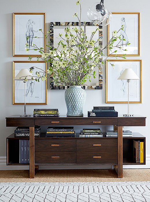 A media console serves as an artful showcase beneath illustrative figure drawings that soften the cabinet's strong lines.