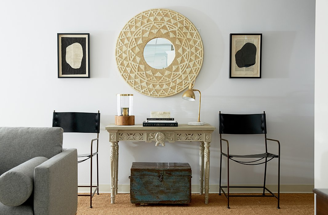 "Among Alex's favorite vignettes in The Studio is this high-contrast display arranged with black leather-and-iron chairs, antique art, a raffia mirror, and an ornate carved console. ""It's wiping out a lot of color, but you're juxtaposing a lot of elements."""