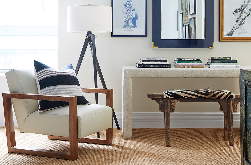 An angular grain-leather armchair is joined by a tripod lamp, an upholstered desk, and a vintage bench punched up with a zebra print, bringing sharp focus to this corner vignette.