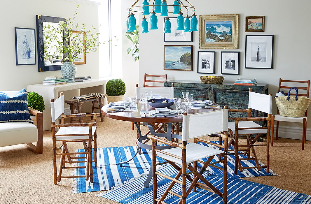 Shades of blue and white plus a hint of turquoise usher in a breezy vibe in the dining area, which features bamboo-and-rattan director's chairs atop striped flat-woven rugs.
