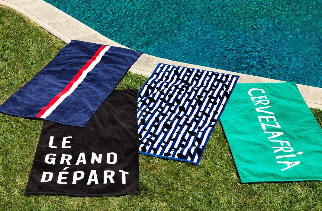 Clare V.'s new collection of beach towels includes her signature stripe, a spirited spot, and two text designs inspired by her travels.