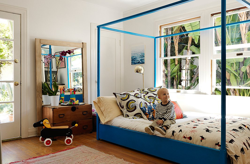 "Son Alfie sits on a four-poster bed in its latest incarnation. ""It used to be a guest bed, so we just cut off the legs,"" says Heidi. ""It has been at least six colors; I call this shade 'shaping room blue'—it's the color of my dad's shaping room."" The throw was found at the Echo Park Craft Fair, and the chest used to house tools in the garage."
