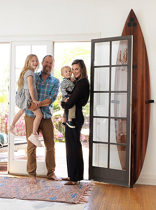 """Heidi with Johnny, Hiver, and Alfie in their 1920s Spanish home. The surfboard was made by her father, surf icon and board shaper Al Merrick. """"He made a few of them from a 3,000-year-old redwood. My brother and I both have one."""""""