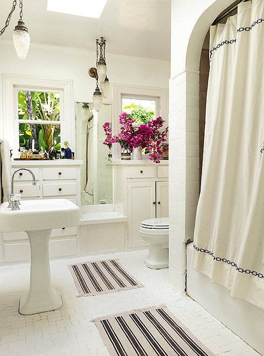 "The bath has original built-ins and Batchelder tile. ""I painted it all white,"" says Heidi. ""People gasp, 'You painted it? That tile is iconic!' But it was brown, and I didn't like it. It is still there."" Heidi found Moroccan-style pendants to go with the mats and the embroidered shower curtain. Bougainvilleas from the garden fill a rustic pitcher."
