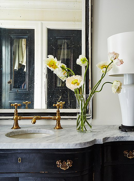 "An antiqued mirror and gold fixtures are intermingled with white porcelain lamps on the sink vanity in the master bath, which is divided into a dressing room, a water closet, and a shower and tub room. ""It was designed with a certain traffic mentality for getting ready quickly,"" Darryl says of tailoring the space to fit his busy daily life."