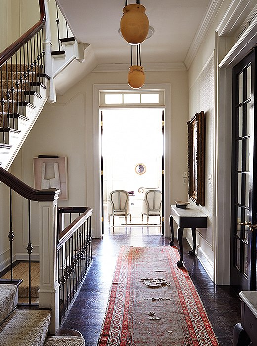 "The airy second-floor landing, with its antique alabaster pendants and a gorgeous distressed runner, captures Darryl's love of timeworn treasures that are none too precious. ""My dog has done quite a number on all of my floors, both wood and stone."""