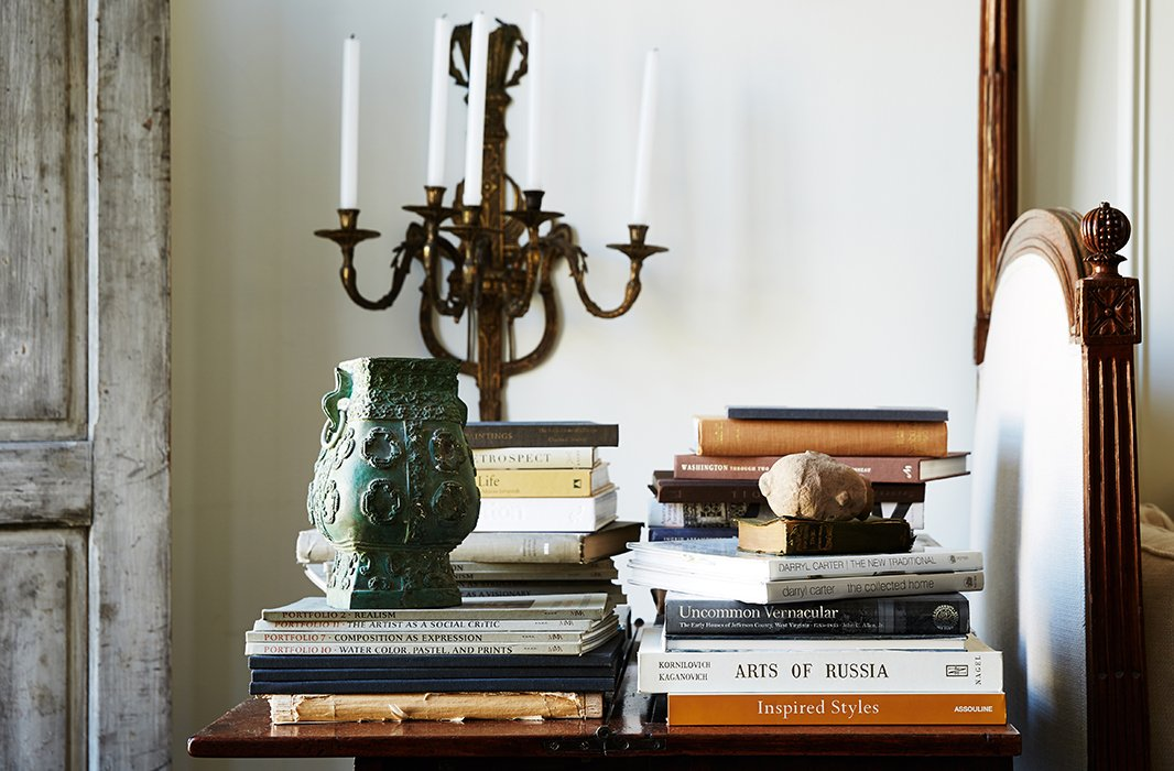 "In the lower sitting room, small stacks of Darryl's favorite art and design books are joined by an eye-catching bronze vase that was ""a precious gift from my father."""