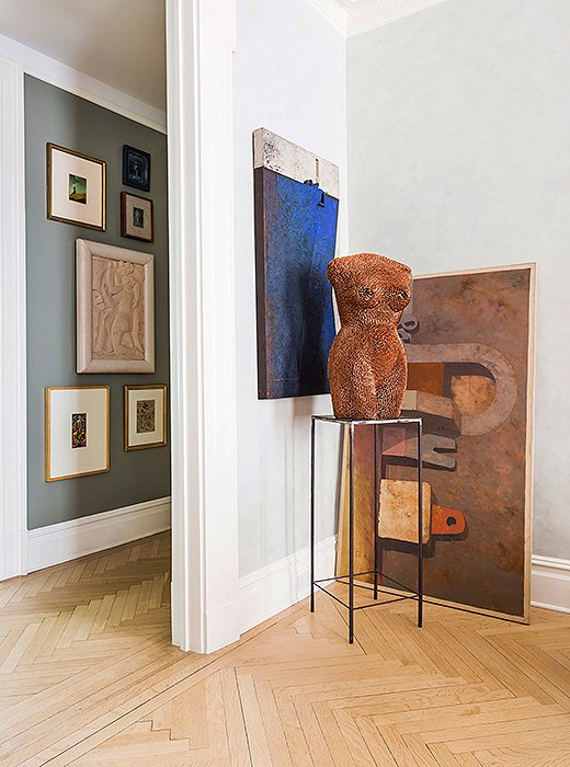 In this gallery-style corner, a simple metal pedestal allows a figurative sculpture to take the spotlight. Photo by Lesley Unruh.