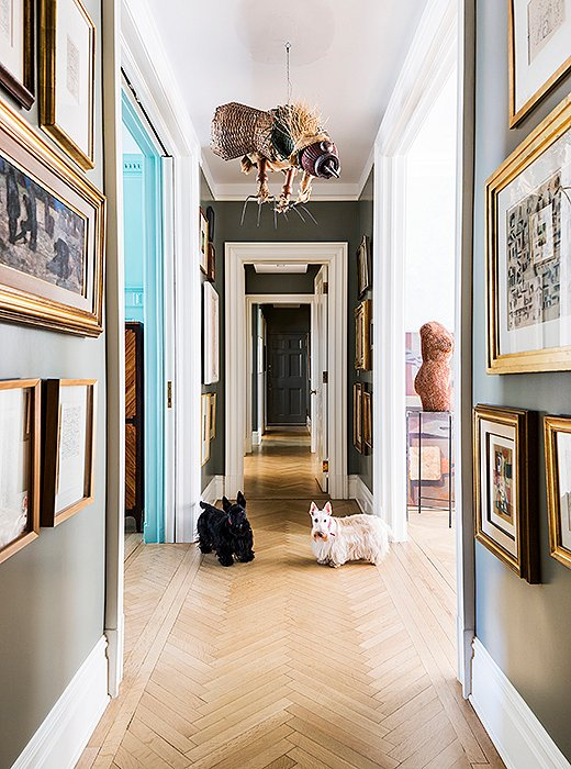 "The hallway is dedicated to artwork, from the bird sculpture by Antonio Berni that hangs overhead to the collection of smaller framed pieces that line the walls salon-style. The paint color is what Roberta calls ""museum gray,"" a dusky greenish gray tone that makes the small paintings—and Roberta's black and white Scottish terriers, Alfa and Romeo—stand out."