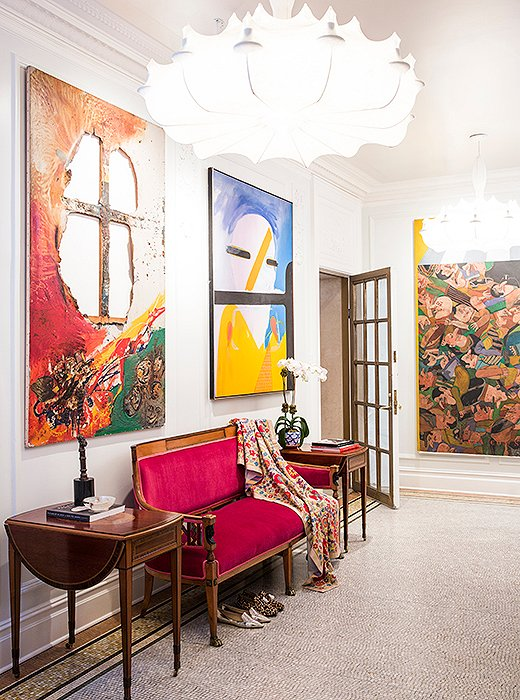 """The entrance to me is like an art gallery,"" says Roberta of her apartment's foyer, where several large works have pride of place. ""You should be able to just sit down and look at the paintings if you want to."" Rich burnished woods and a velvet-upholstered settee—backed with a vintage Indian textile—warm up the crisp white walls and mosaic-tile floor."