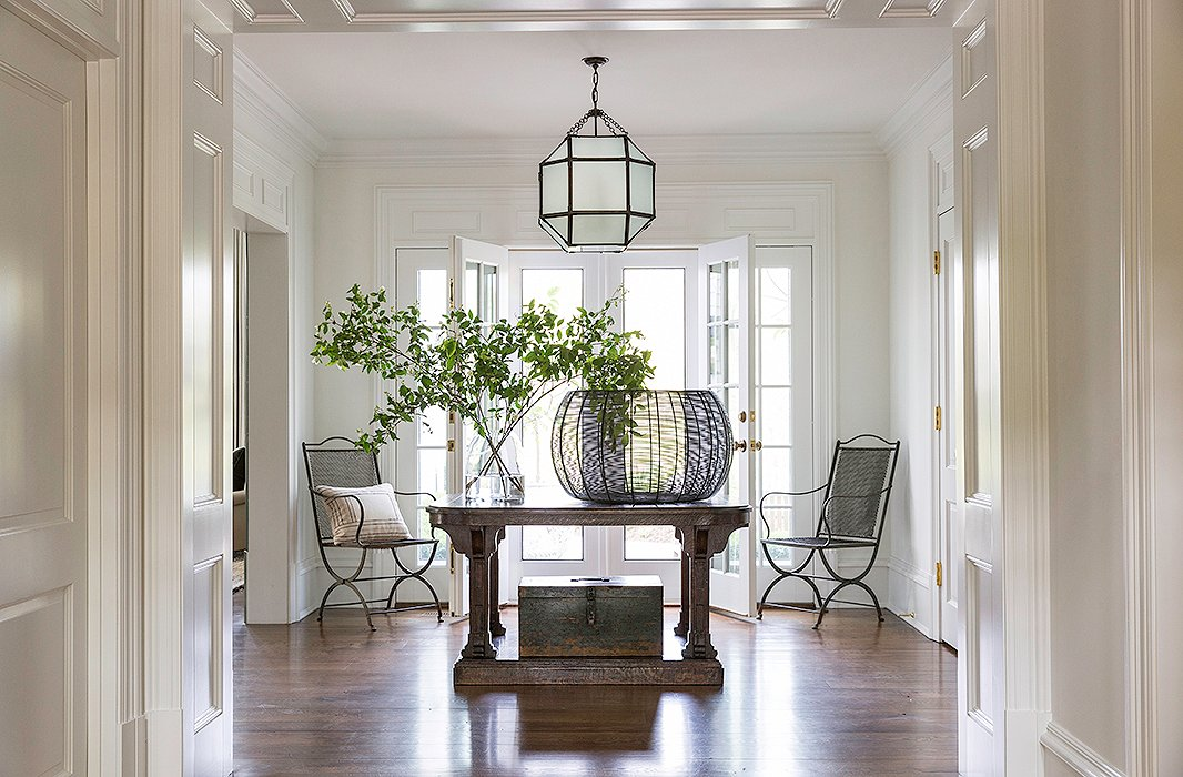 With a center table, a pair of antique chairs, and a lantern by Suzanne Kasler, the house's grand entrance hall is airy and inviting.