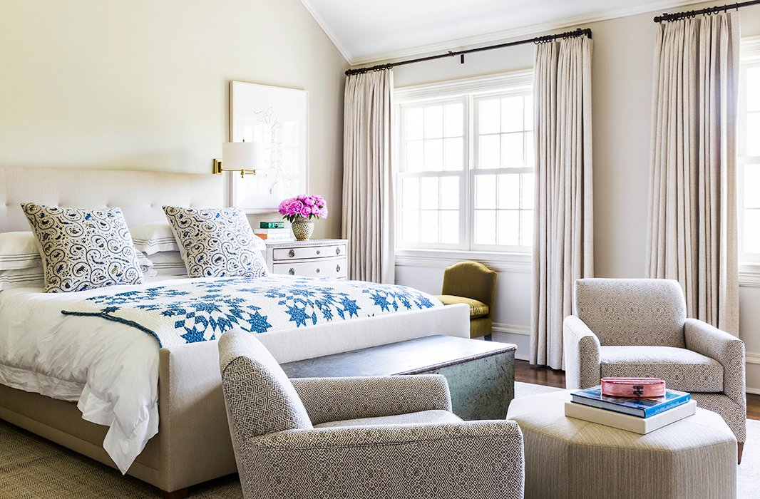 Theairy master bedroom features a large lithograph by Ellsworth Kelly and a handmade quilt fromPaula Rubenstein. A green velvet children's chair serves as the perfect place to put on shoes.